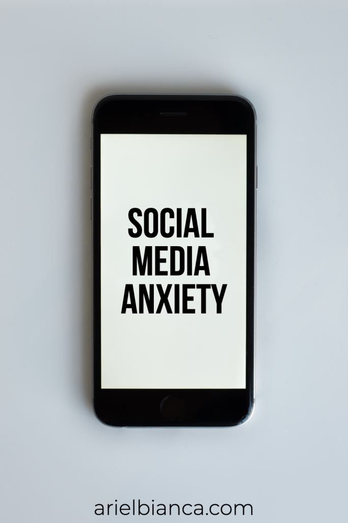 A black cell phone with social media anxiety written on it in a black font. The background is white and the cell phone's background.